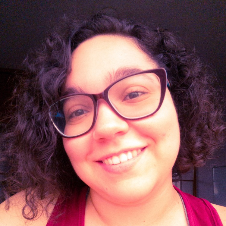 Retrato de Mayara Barros, uma mulher branca, de cabelo cacheado curto, olhos castanhos, óculos.