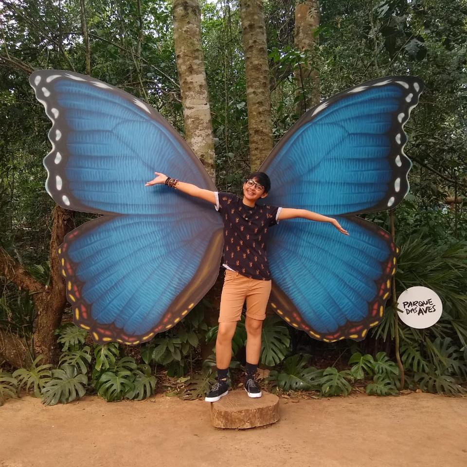 Foto de Mojo, contra uma escultura de asas de borboletas no Parque das Aves, posando de braços abertos. Veste uma blusa escura, short bege, tênis e meias pretas. Usa o cabelo curto e preto e tem pele clara.